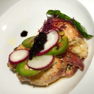 Butter poached lobster with sliced radish and jalapeños.